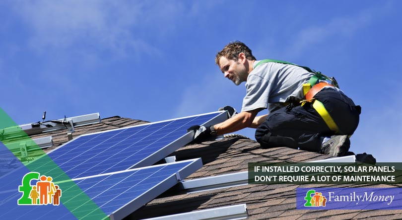 A picture of a qualified fitter installing solar panels on the roof of a house