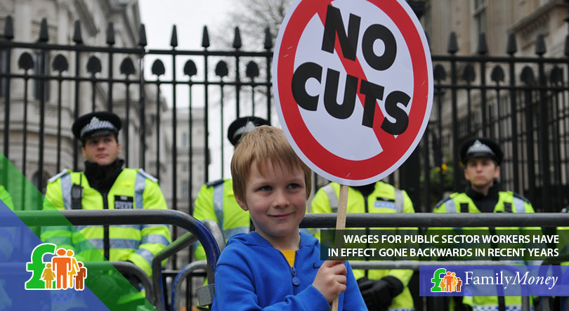 A boy holding a sign at a demonstration protesting cuts to wages