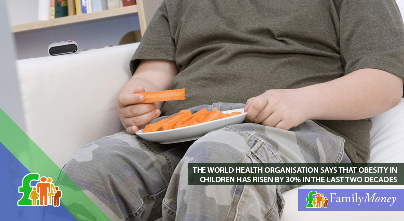 A obese child is sitting on an armchair holding a plate of carrots