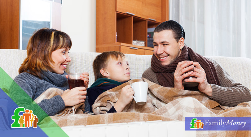 A family are sitting on the sofa under a blanket