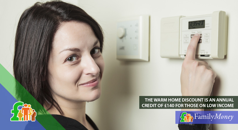 A woman adjusts the thermostat in her home to help save money on energy bills