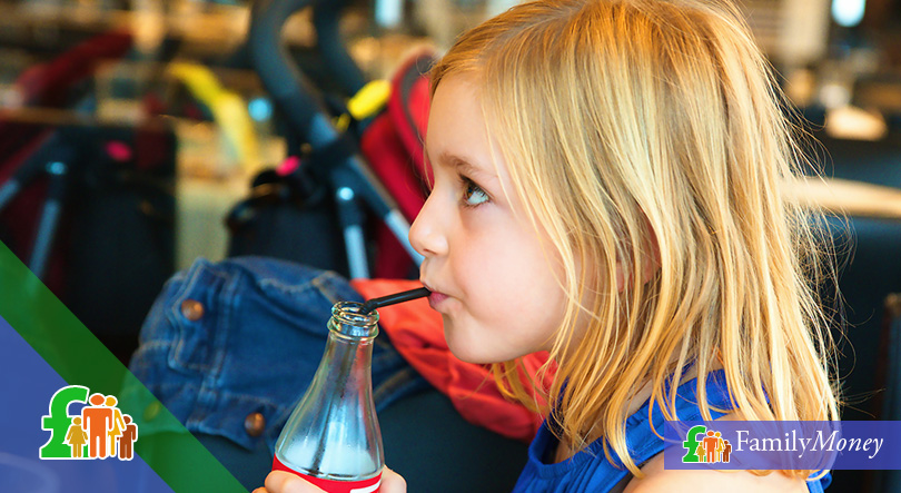 A girl is drinking a soft drink with a straw