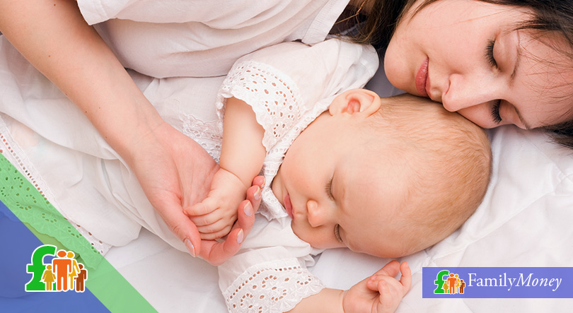 A mother and her baby are lying down on the bed