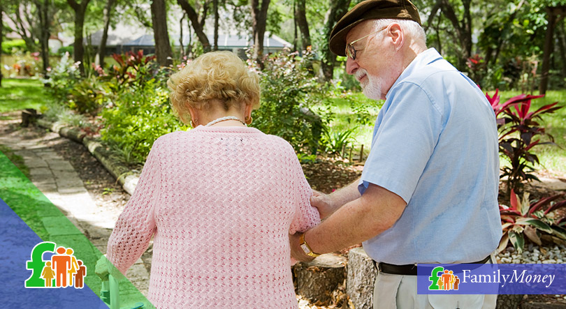 A senior caretaker is looking after an elderly lady at a park