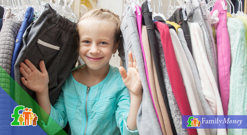 Girl standing in between clothes on a rack.