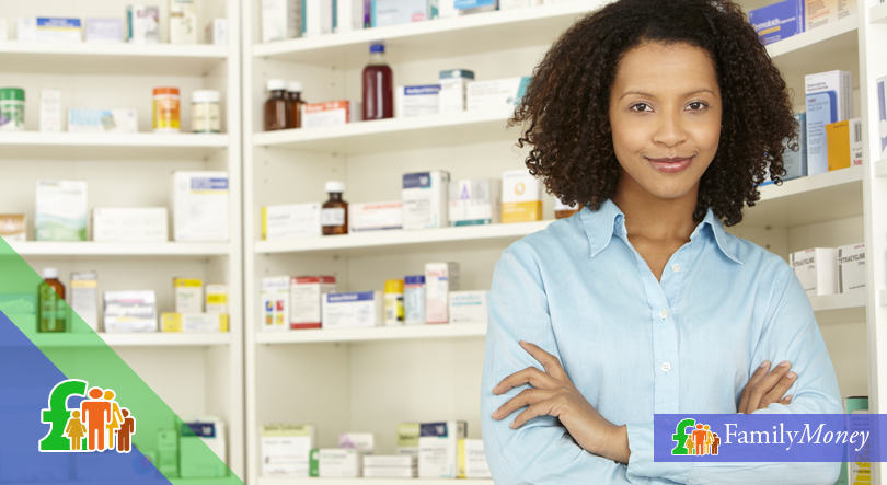 A pharmacist shown at work standing in front of medicine on shelves