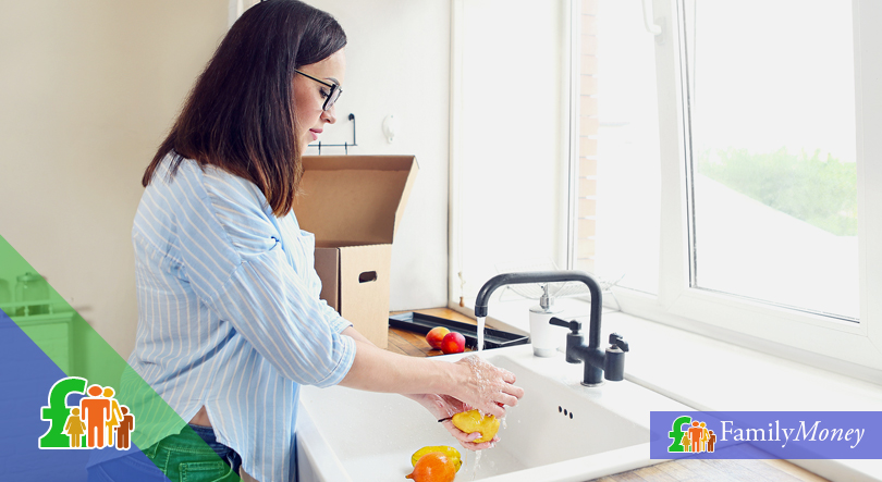 Woman in the kitchen washing fruit.