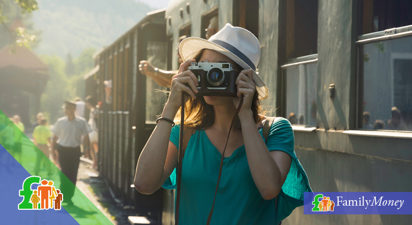 A woman who is traveling takes pictures at a train station