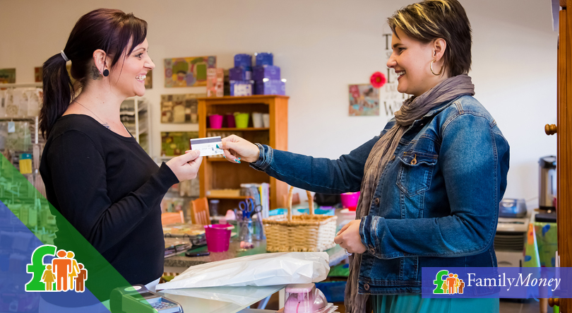 A woman is shown using her credit card at a shop