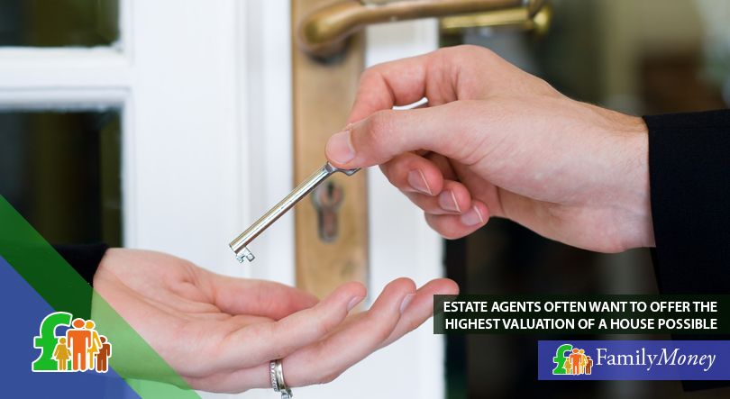 An estate agent hands their customer a key to their new house