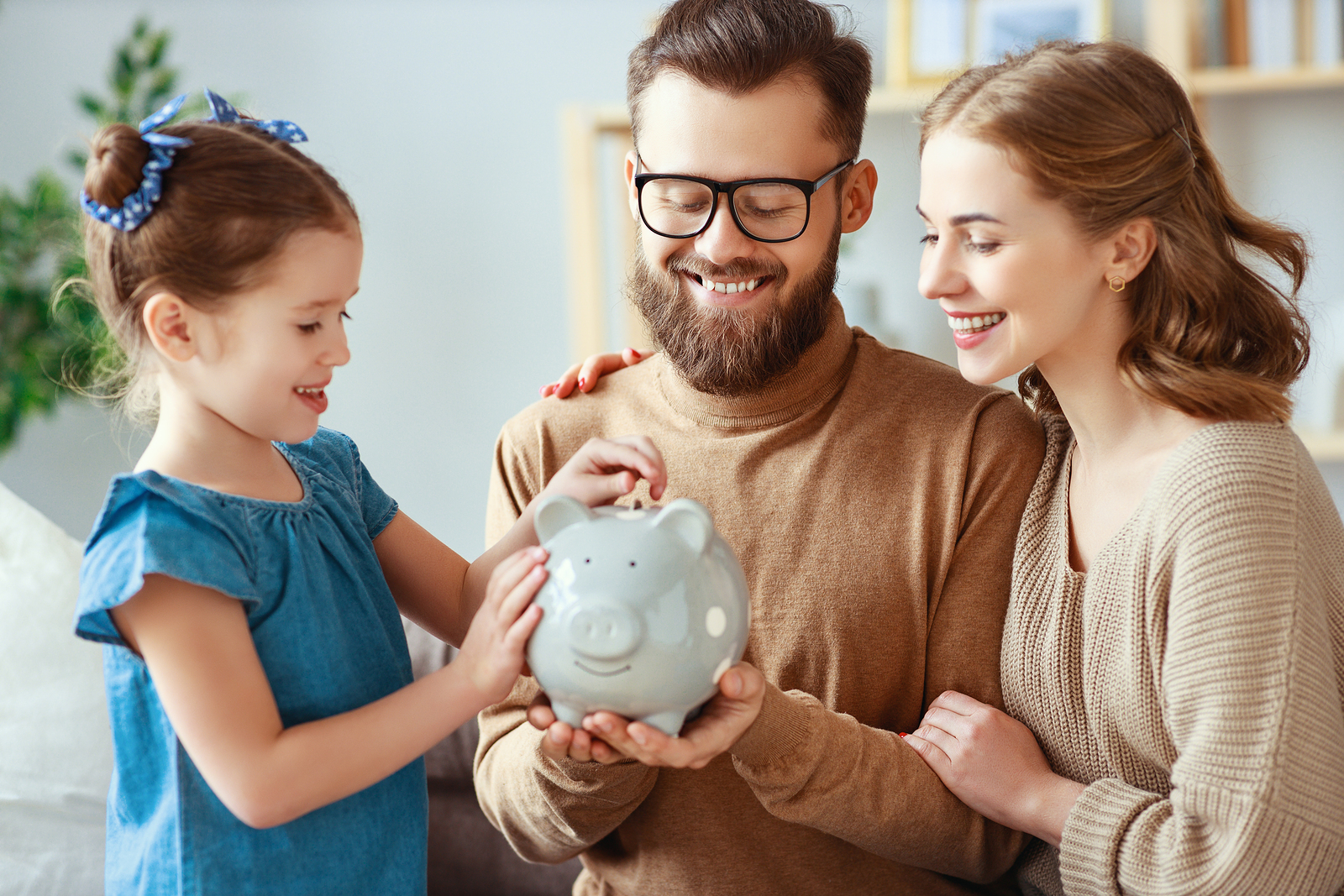 A family is shown holding a piggy bank