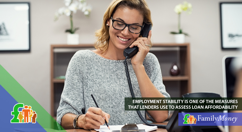 A woman is shown is working in an office environment while talking on the phone with a loans company